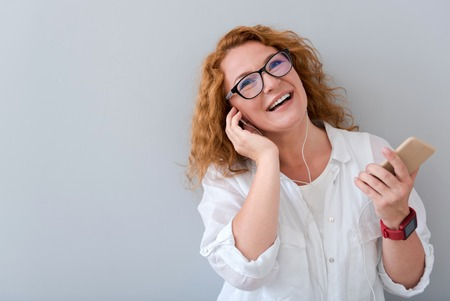overjoyed: Just relax. Overjoyed smiling beautiful woman wearing headphones and holding cell phone while listening to music