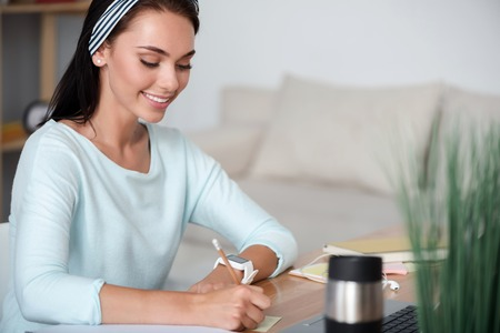 Positive worker. Pleasant delighted smiling woman sitting at the table and making notes Stock Photo