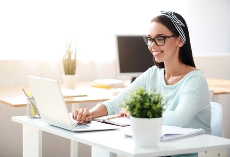 영감을 가지고 노력하십시오. 노트북을 사용 하 고 테이블에 앉아있는 동안 사무실에서 일하고 쾌활 한 아름 다운 여자를 기쁘게 생각 스톡 콘텐츠