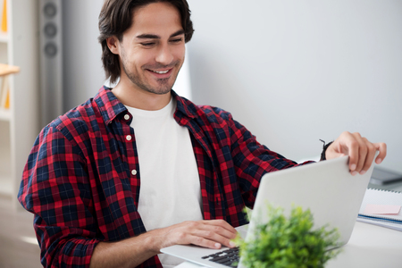 manhood: Modern user. Cheerful handsome smiling man sitting at the table and using laptop while working in the office Stock Photo