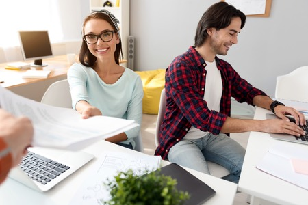 manhood: That is for you. Pleasant beautiful smiling woman sitting at the table and giving paper while working with her colleague Stock Photo