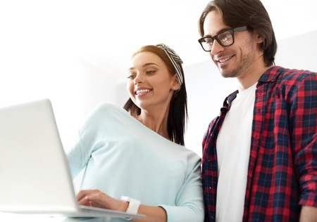 modern generation: Modern generation. Cheerful delighted colleagues smiling and using laptop while working on the project Stock Photo