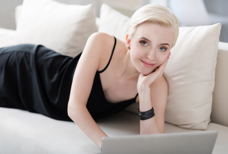 After a hard day. Joyful elegant young woman looking at the camera while using his laptop and lying on the couch