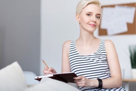 rigor: Calm time. Thoughtful relaxed adorable woman looking at the camera while sitting on the sofa and writing in the notebook