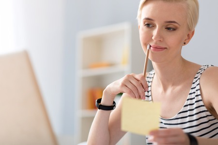 verifying: Involved in work. Pensive cute young woman touching her lips with a pencil while holding a paper and verifying some details on her laptop
