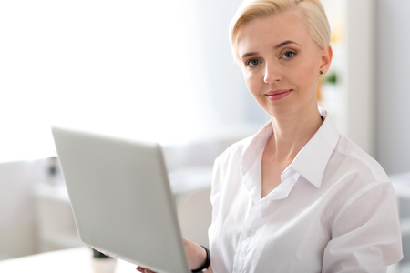 liable: Like what you do. Elegant young woman looking at the camera while standing and holding a laptop