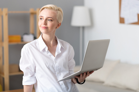 Have a look. Cheerful confident worker standing and holding a laptop while looking aside and smiling