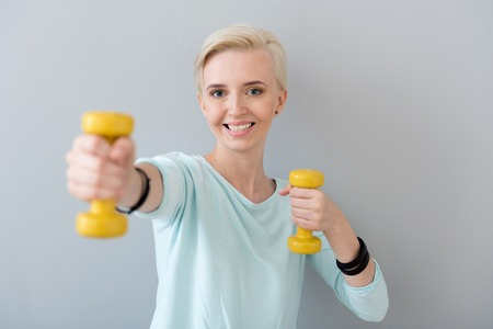 contended: To stay in a good shape. Adorable healthy young woman doing some exercises with dumbbells isolated on the grey background