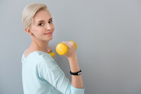 contended: Sport is a power. Energetic healthy young woman looking at the camera while doing some exercises with dumbbells isolated on the grey background Stock Photo