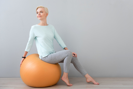 contended: Healthy body and healthy mind. Gorgeous young woman looking aside while sitting on the fitball isolated on the grey background Stock Photo
