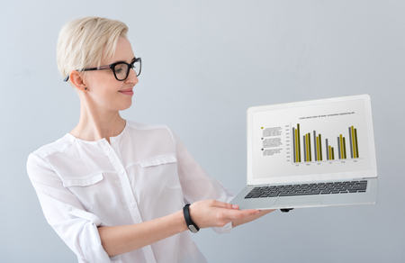 liable: Have a look. Clever woman with glasses holding a laptop with diagram on the screen and looking at it