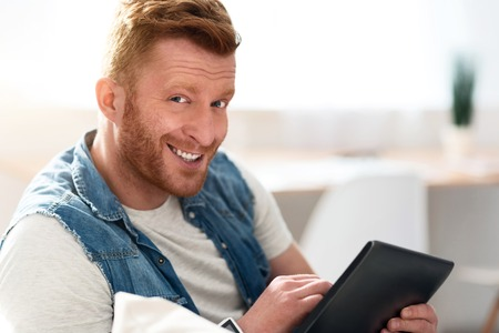 manhood: Playful mood. Joyful handsome smiling man sitting on the couch and expressing gladness while using tablet