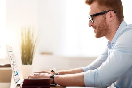 diligente: trabajador diligente. Agradable hombre guapo involucrados sentado en la mesa y utilizando equipo portátil mientras se escribe