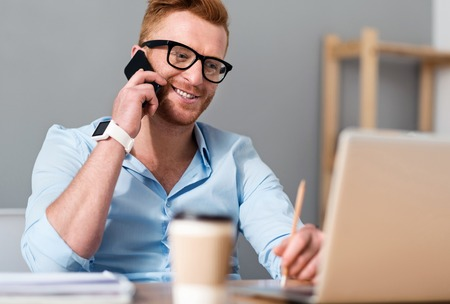 Get in Touch. Cheerful handsome smiling man sitting at the table and talking on cell phone while working Stock Photo