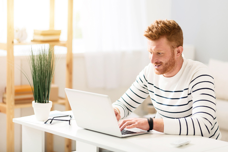 manhood: Full of gladness. Cheerful handsome involved man sitting at the table and smiling while using laptop