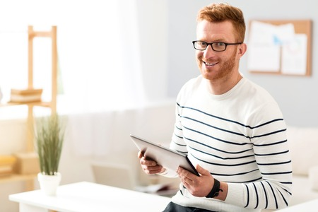gladness: Modern user. Pleasant joyful smiling ma leaning on the table and holding tablet while expressing gladness Stock Photo