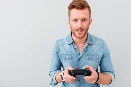 users video: Involved in process. Cheerful delighted bearded man holding game console and playing video games while standing isolated on grey background