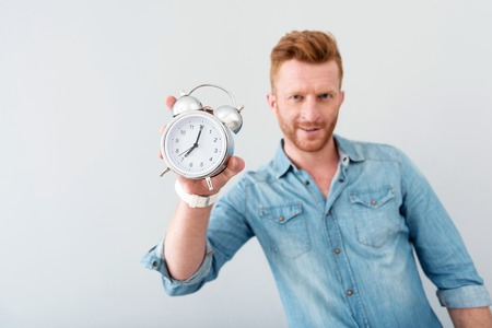 save time: Save time. Close up of alarm clock n hands of pleasant delighted man holding it while standing isolated on grey background Stock Photo