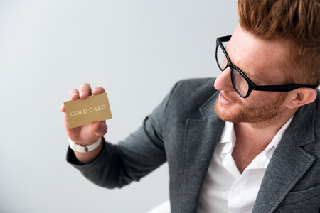 man holding card: Regular customer. Positive handsome man holding card and smiling while standing isolated on grey background
