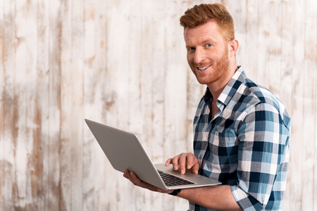 manhood: Technologically addicted. Cheerful content man smiling and using laptop while standing isolated on wooden background