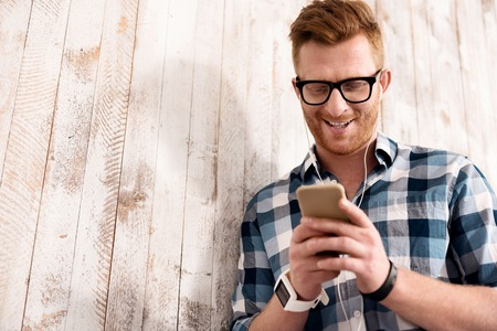 enjoyable: Enjoyable time. Cheerful content smiling man holding cell phone ad listening to music while leaning on the wooden wall