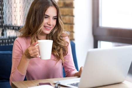 potěšen: IN a good mood. Cheerful delighted beautiful woman drinking coffee and using laptop while sitting at the table
