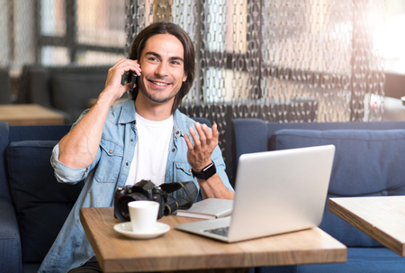 gladness: Call me back. Joyful smiling man talking on cell phone and sitting at the table while expressing gladness