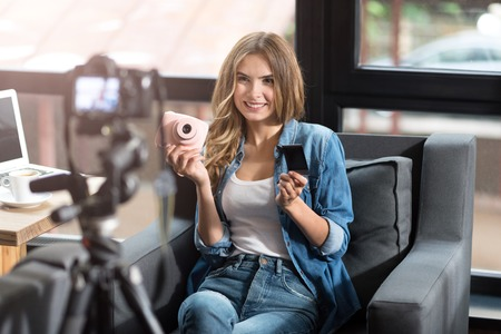 Moderne Blogger. Fröhlich erfreut lächelnde Frau auf der Couch sitzen und das Gefühl, Inhalt, während eine Videoaufnahme Standard-Bild - 61352833