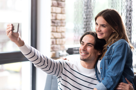 say cheese: Say cheese. Joyful delighted couple smiling and making selfies while while resting in the cafe Stock Photo