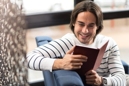 Full of gladness. Cheerful handsome content man sitting on the settee and reading book while resting in the cafe Stock Photo