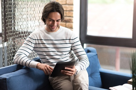 In touch with technologies. Cheerful handsome smiling man sitting on the settee and using tablet while resting