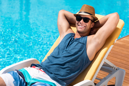 bathing man: Endless summer . Handsome positive delighted man lying on the sunbed and resting near pool while sun bathing