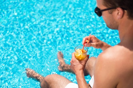booster: Energy booster. Close of cocktail in hands of pleasant handsome man holding it and going to drink while sitting near swimming pool