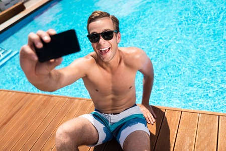 overjoyed: Just smile. Overjoyed handsome smiling man sitting near swimming pool and holding cell phone while making selfies Stock Photo