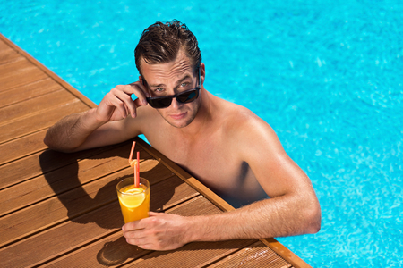 Magnetic glance. Pleasant handsome man sitting in the swimming pool and drinking cocktail while looking at you Stock Photo