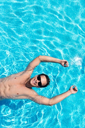 overjoyed: Live fully. Overjoyed delighted handsome man smiling and relaxing while swimming in a pool Stock Photo