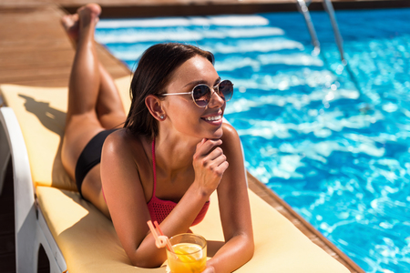 eager: Eager to rest. Positive delighted smiling woman drinking cocktail and lying on the sun bed while resting near swimming pool Stock Photo
