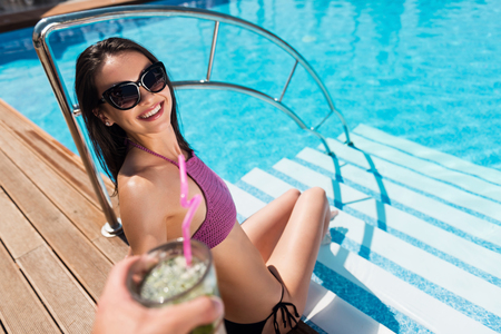 Feel summer days. Cheerful delighted young woman smiling and sitting near swimming pool while someone giving her a cocktail Stock Photo