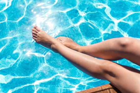 Sunny days. Pleasant slim woman sitting in the swimming pool and holding legs in the water Stock Photo