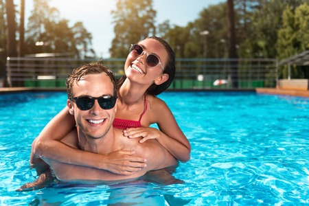 overjoyed: Happy together. Delighted overjoyed couple smiling and embracing while swimming in a pool