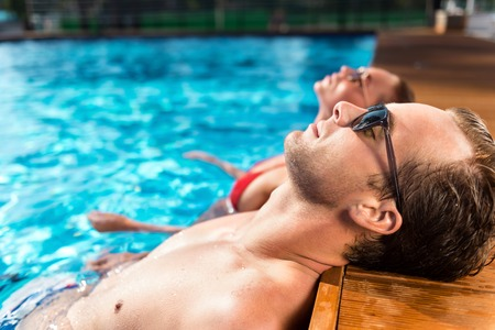 revel: Revel in sunny days. Pleasant delighted loving couple lying in the swimming pool and resting Stock Photo