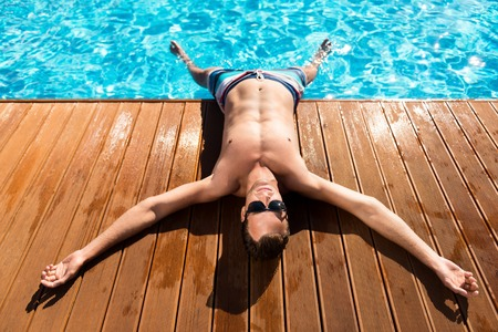 vocation: Look forward to vocation. Cheerful delighted handsome man lying near swimming pool and resting