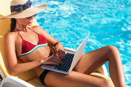 delighted: Break for work. Pleasant delighted beautiful woman sitting in the sun bed and using laptop while resting near swimming pool Stock Photo