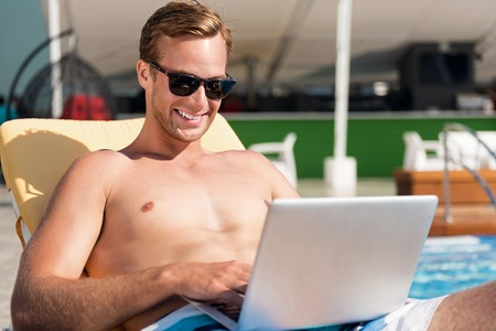 Involved in digital world. Cheerful handsome smiling man lying on the sun bed and using laptop while resting near swimming pool Stock Photo