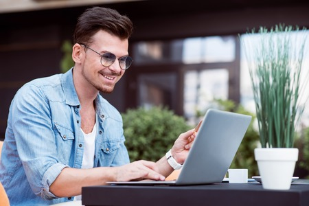 gladness: Full of gladness. Positive smiling handsome man sitting at the table and using laptop while resting in the cafe Stock Photo