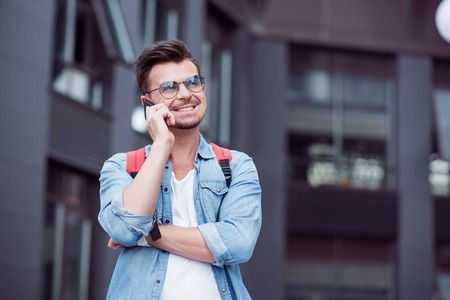 expressing joy: Nice to hear you. Cheerful handsome young man talking on cell phone and standing in the street while expressing joy Stock Photo
