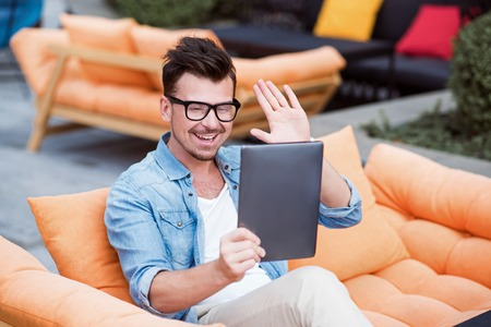 Hey. Positive content handsome man sitting on the couch and talking through the Internet while using tablet