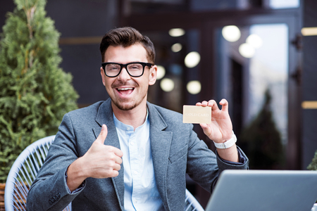 Full of positivity. Overjoyed content handsome man smiling and thumbing up while holding gold card