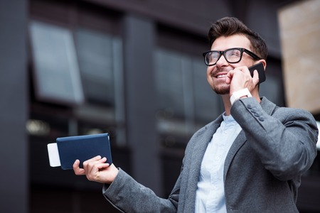 important phone call: Important call. Pleasant joyful smiling man holding purse and talking on cell phone while standing near office building Stock Photo