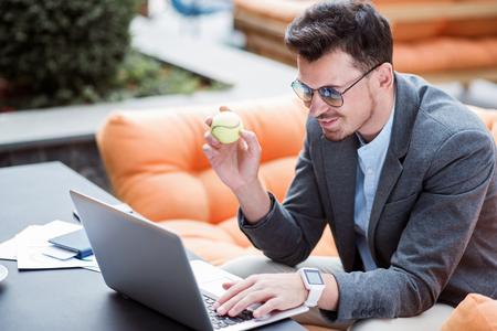 tabla de surf: Navegar por internet. Encantados hombre de negocios sentado en la mesa y la celebración de una pelota de tenis, mientras que usando la computadora portátil Foto de archivo